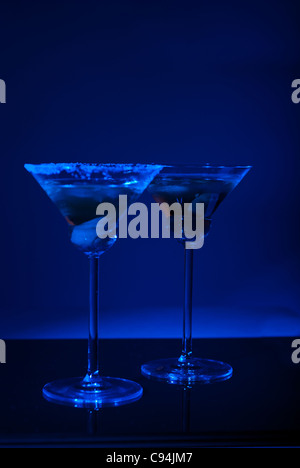 Two martini glasses with olives in darkness with blue light - Stock Photo