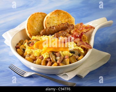 A breakfast skillet of potatoes, mushrooms and onions covered with eggs and cheese and served with bacon, sausage - Stock Photo