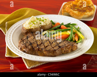 Rib eye steak served with a loaded baked potato, vegetables and garlic bread - Stock Photo