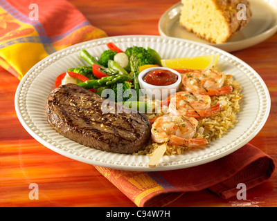 Sirloin and grilled shrimp dinner over rice served with vegetables - Stock Photo