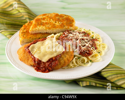 Chicken Parmesan dinner with pasta served with garlic bread - Stock Photo