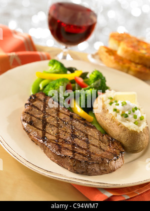Steak dinner served with a loaded baked potato, vegetables, garlic bread and a glass of wine - Stock Photo