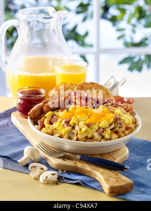 Scrambled egg and ham skillet breakfast served with sausage, bacon, toast and orange juice - Stock Photo