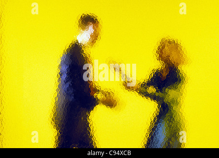 Abstract view of businessman and businesswoman through mottled glass wall - Stock Photo