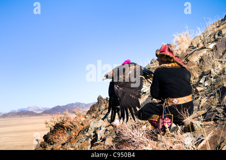 Kazakh eagle hunter sends out his golden eagle to fly in the Altai Region of Bayan-Ölgii in Western Mongolia. - Stock Photo