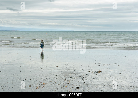 Woman at Criccieth beach in Wales, UK - Stock Photo
