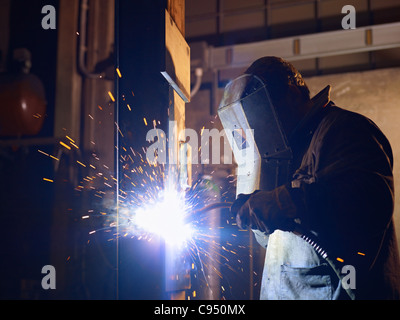 Manual worker in steel factory using welding mask, tools and machinery on metal. Horizontal shape, side view, waist - Stock Photo