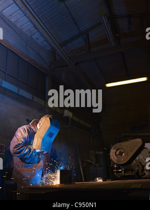 Manual worker in steel factory using welding mask, tools and machinery on metal. Vertical shape, side view, waist - Stock Photo