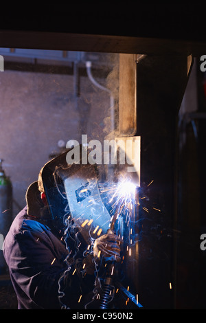 Manual worker in steel factory using welding mask, tools and machinery on metal. Vertical shape, side view, copy - Stock Photo