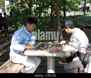 Asian men playing chinese chess in Columbus park in Chinatown, NYC - Stock Photo