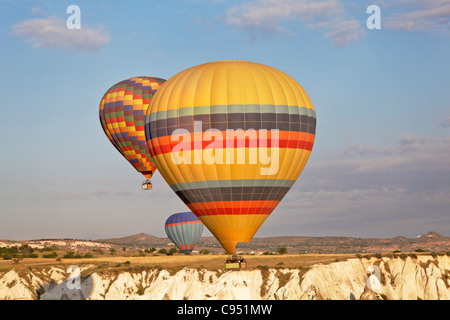 landscape three multi colored hot air balloons low level flight over Cappadocia cliffs, early morning sun, blue - Stock Photo