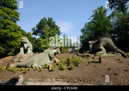 Dinosaur statues made of stone amoungst trees in dinosaur court at Crystal Palace park, South East London. - Stock Photo