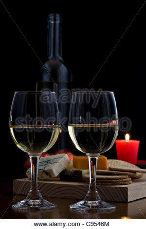 Two glasses of white wine with cheese selection and biscuits on wooden board with red candle on dark background - Stock Photo