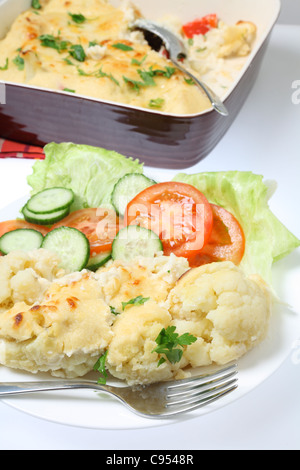 A plate of cauliflower cheese or gratin served with a salad of tomato, lettuce and cucumber, with the serving bowl - Stock Photo