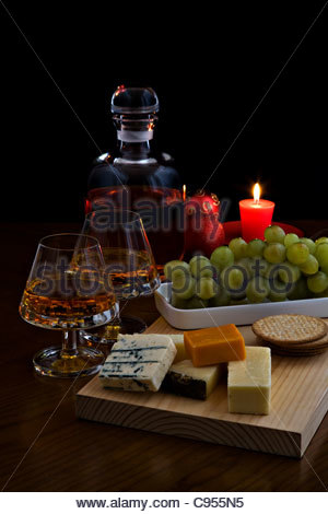 Two glasses of brandy with decanter, cheese selection, biscuits, grapes and red candle on dark background with Christmas - Stock Photo