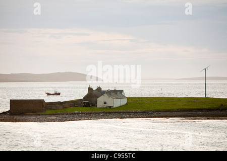 A small scale wind turbine powering a house on Outer Holm island off Stromness in Orkney, Scotland, - Stock Photo