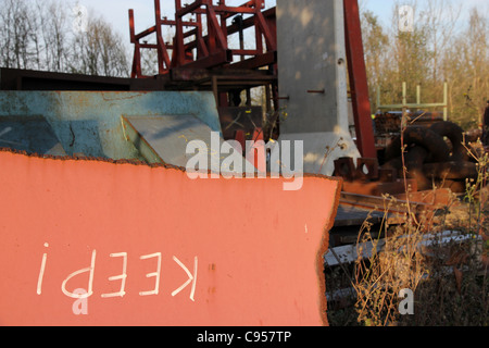 ironic Keep notice on scrapped metal, scrap metal yard of engineering firm - Stock Photo
