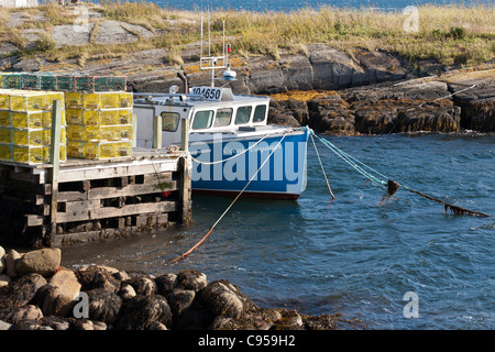 Ocean Voyager and Lobster Pots. A blue fishing boat tied up to a wharf covered with modern lobster pots. - Stock Photo