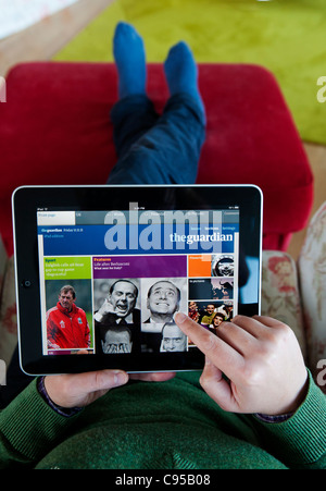 Woman using iPad tablet computer to read The Guardian newspaper online edition - Stock Photo