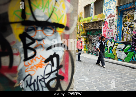 Tourists looking at street art in Hosier Lane.  Melbourne, Victoria, Australia - Stock Photo