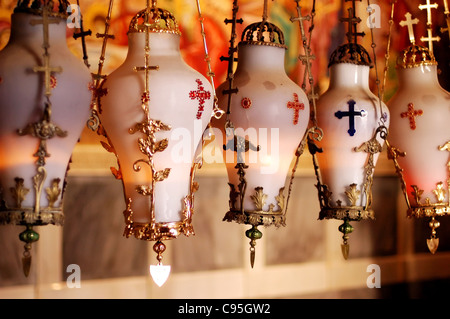 Lamps hang above the Stone of the Anointing in the Church of the Holy Sepulchre, Jerusalem old city, Israel. - Stock Photo