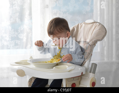 One and a half year old boy sitting in a high chair and eating soup with a spoon, spilling it on his shirt - Stock Photo