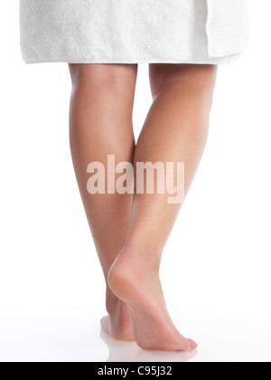 Closeup of legs of a young woman wrapped in a towel. Isolated on white background. - Stock Photo