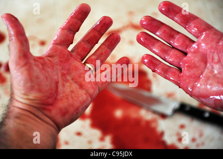 Conceptual image of hands of a married man with a wedding ring are covered in blood - Stock Photo