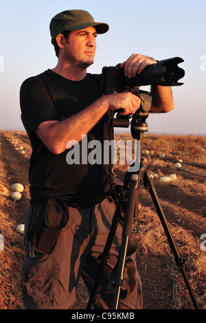 A photographer is standing and looking at the landscape of a field near a camera on a tripod with a zoom lens to - Stock Photo