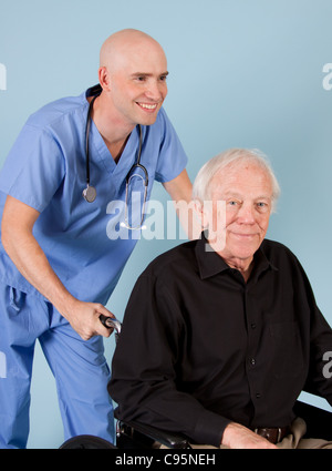 Elderly man in wheel chair and medical worker. - Stock Photo