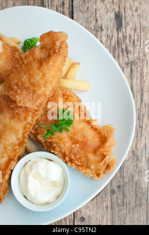 Two battered fish fillets on a plate with chips and mayonnaise - Stock Photo