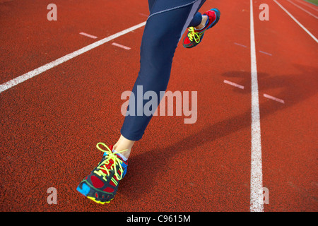 Running. Close-up of the legs of a woman running on an athletics track. - Stock Photo