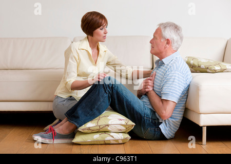 Man having a heart attack. The woman is placing him in a comfortable position until help comes. - Stock Photo