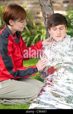 Hypothermia. Woman wrapping a boy in a foil blanket to warm him up. - Stock Photo