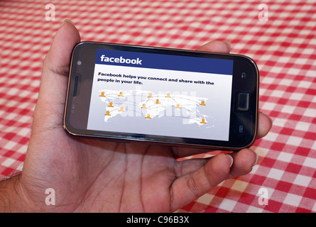Person holding a smart phone displaying the home page of facebook website - Stock Photo