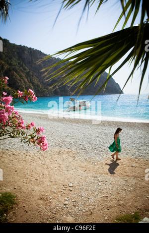 Girl in green dress walking on beach - Stock Photo