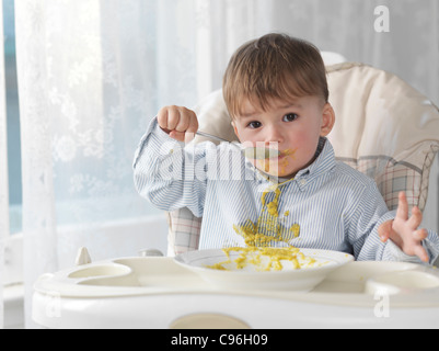 Cute baby boy sitting in a high chair and eating soup with a spoon, spilling it on his shirt - Stock Photo