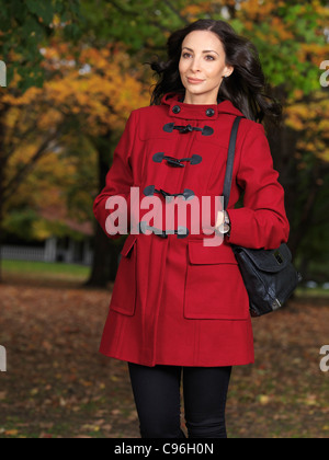 Beautiful young woman walking along the street in fall nature wearing a red coat - Stock Photo