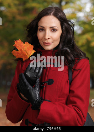 Portrait of a beautiful woman holding a red maple leaf in her hands - Stock Photo