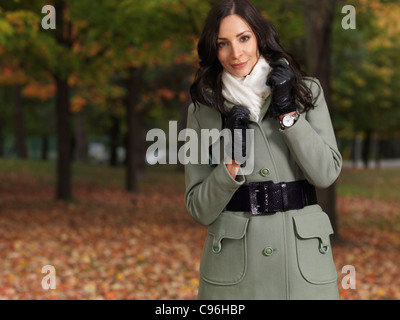 Beautiful smiling woman wearing a green coat walking through a park in fall - Stock Photo