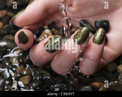 Closeup of woman hand with green fancy nail polish in water on pebble stones - Stock Photo