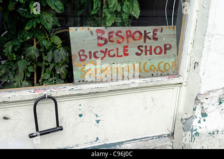 Sign saying 'Bespoke' Bicycle Shop in corner of shop window with u lock hanging from wall outside, Sargent and co, - Stock Photo