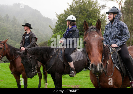 Horseman on dirt path surrounded by thick vegetation, doing a guided tour - Stock Photo