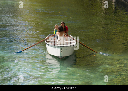 Two young French women in a rowing boat with a small boy. - Stock Photo