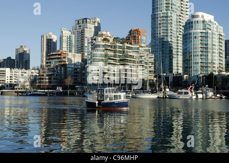 With Yaletown in the background a water taxi is eastbound on the waters of False Creek, Vancouver. - Stock Photo