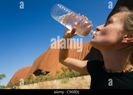Hiker drinking water on the Uluru (Ayers Rock) Base Walk.  Uluru-Kata Tjuta National Park, Northern Territory, Australia - Stock Photo