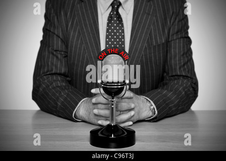 Photo of a news broadcaster sat at a desk and retro microphone with an On The Air illuminated sign - Stock Photo