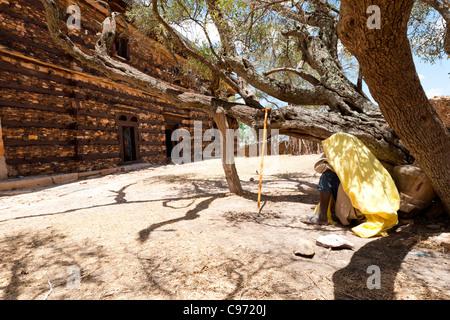 An Orthodox Christian pilgrim praying outside Abuna Aregawi Church at Debre Damo in Tigray, Northern Ethiopia, Africa. - Stock Photo