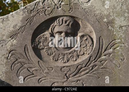 Cherub on gravestone, St. Leonard`s churchyard, Over Whitacre, Warwickshire, England, UK - Stock Photo