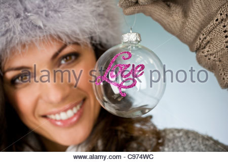 A young woman holding a glass bauble - Stock Photo